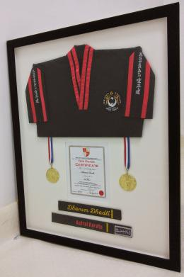 Framed karate shirt certificate and medals