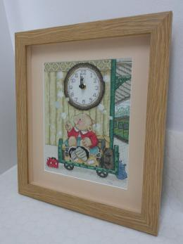 Framed needlework with working clock mechanism